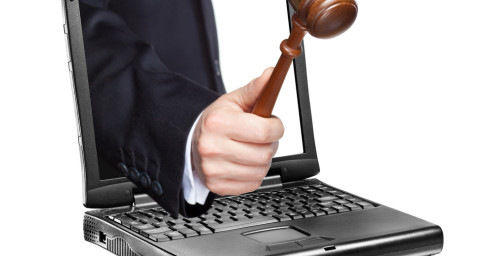 a hand reaches out of a laptop with a wooden hammer